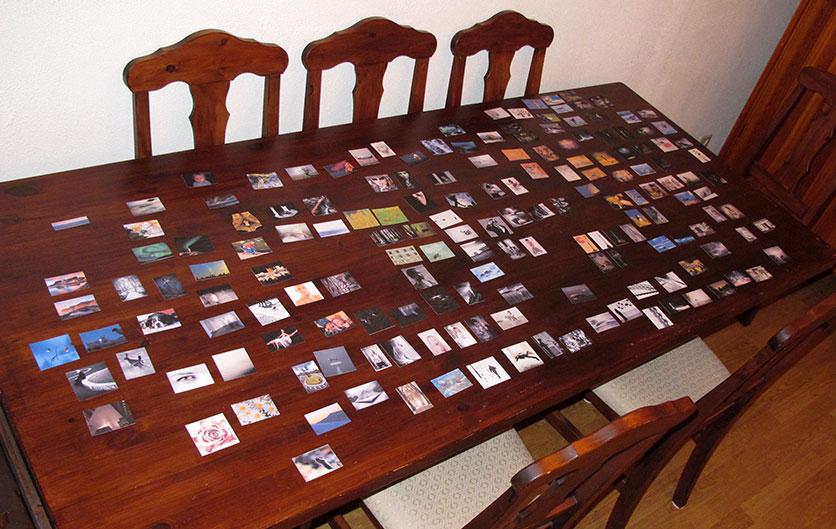 Arbeidet med Årboken 2012. Bilder spredt på bordet før hvit kartong er plassert under.